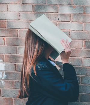 Pupil with book over face in front of brick wall